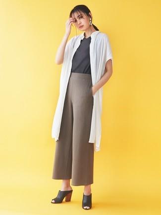 Cómo combinar: abrigo duster blanco, camiseta con cuello circular en gris oscuro, pantalones anchos de punto marrónes, chinelas de cuero negras