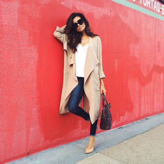 Cómo combinar: abrigo duster marrón claro, camiseta con cuello en v blanca, vaqueros pitillo azul marino, zapatos de tacón de cuero marrón claro