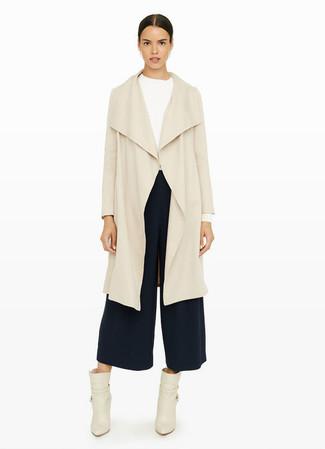 Cómo combinar: abrigo duster en beige, camiseta de manga larga blanca, falda pantalón azul marino, botines de cuero en beige