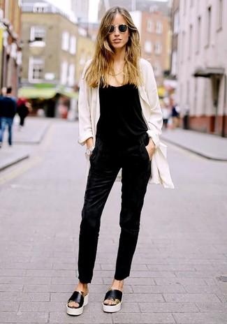 Cómo combinar: abrigo duster blanco, mono negro, sandalias planas de cuero en negro y blanco, gafas de sol negras