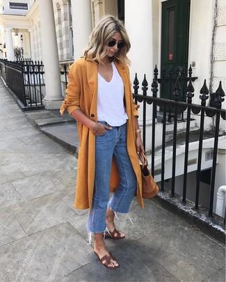 Cómo combinar: abrigo duster naranja, camiseta con cuello en v blanca, vaqueros azules, sandalias planas de cuero en marrón oscuro