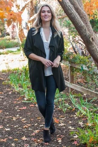 Un abrigo duster negro y unos vaqueros pitillo azul marino son prendas que debes tener en tu armario. Para darle un toque relax a tu outfit utiliza botines chelsea de ante negros.