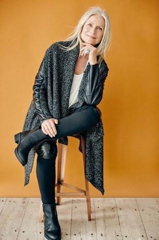 Cómo combinar: abrigo de punto en gris oscuro, camiseta con cuello circular blanca, vaqueros pitillo negros, botines de cuero negros
