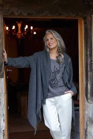 Moda para mujeres de 60 años en clima frío: Intenta ponerse un abrigo en gris oscuro y unos pantalones anchos blancos para después del trabajo.