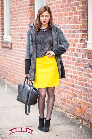 Cómo combinar: abrigo de espiguilla en gris oscuro, jersey con cuello circular de angora en gris oscuro, minifalda de cuero amarilla, botines de ante negros