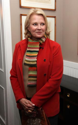 Moda para mujeres de 60 años en clima frío: Elige una apariencia sofisticada en un abrigo rojo y un pantalón de vestir negro.