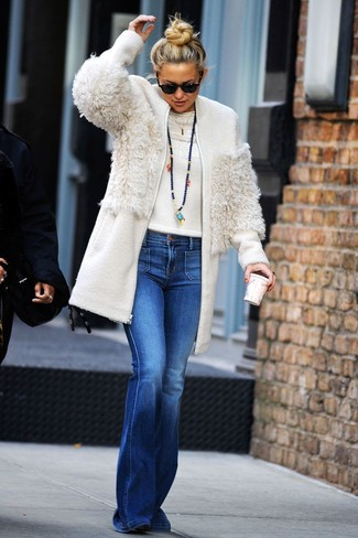 Cómo combinar: abrigo de forro polar blanco, jersey con cuello circular blanco, vaqueros de campana azules, botines de ante negros