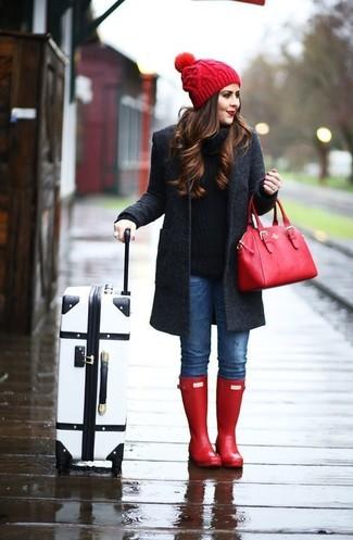 Cómo combinar: abrigo en gris oscuro, jersey con cuello circular negro, vaqueros pitillo azules, botas de lluvia rojas
