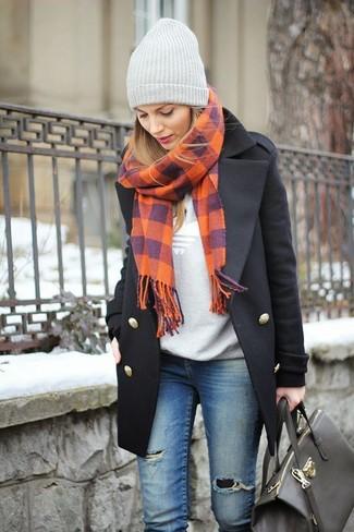 Haz de un abrigo negro y unos vaqueros pitillo desgastados azules tu atuendo para conseguir una apariencia glamurosa y elegante.