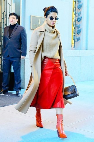 Emparejar un abrigo beige junto a una falda midi de cuero roja es una opción perfecta para un día en la oficina. Completa el look con botines de cuero rojos.