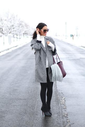 Cómo combinar: abrigo gris, jersey de cuello alto blanco, leggings negros, botines de cuero сon flecos negros