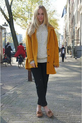 Cómo combinar: abrigo mostaza, jersey de ochos en beige, camisa de vestir blanca, pantalón chino negro