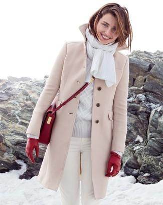 Cómo combinar: abrigo en beige, jersey de ochos gris, vaqueros pitillo blancos, bolso bandolera de cuero rojo