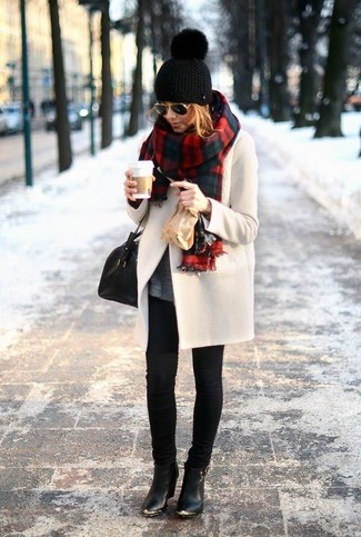 Casa un abrigo beige con unos vaqueros pitillo negros para cualquier sorpresa que haya en el día. Complementa tu atuendo con botines de cuero negros.
