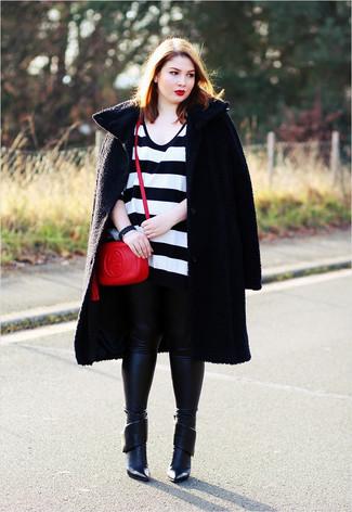 Cómo combinar: abrigo con relieve negro, jersey oversized de rayas horizontales en blanco y negro, leggings de cuero negros, botines de cuero negros