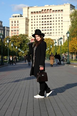 Cómo combinar: abrigo negro, jersey oversized de punto gris, pantalones de pijama de terciopelo negros, tenis de lona blancos