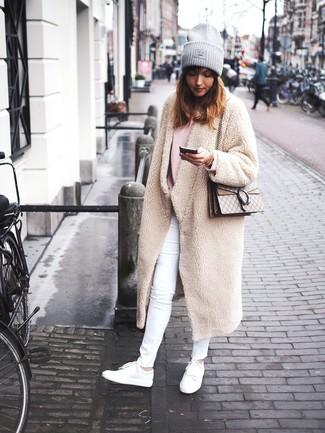 Cómo combinar: abrigo de forro polar en beige, jersey oversized rosado, vaqueros pitillo blancos, tenis de cuero blancos