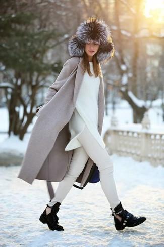 Cómo combinar: abrigo gris, jersey oversized blanco, vaqueros pitillo en beige, botines de cuero con recorte negros