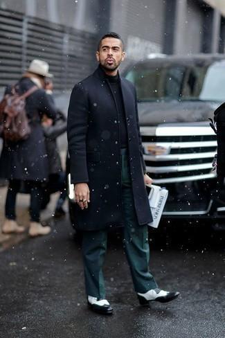 Outfits hombres en clima frío: Algo tan simple como optar por un abrigo largo azul marino y un pantalón de vestir verde oscuro puede distinguirte de la multitud. Para el calzado ve por el camino informal con zapatos brogue de cuero en negro y blanco.