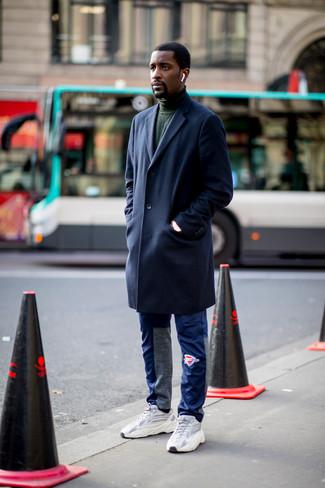 Cómo combinar: abrigo largo azul marino, jersey de cuello alto verde oscuro, pantalón de chándal azul, deportivas grises