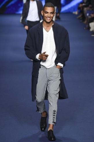 Cómo combinar: abrigo largo azul marino, jersey de pico blanco, pantalón chino de rayas verticales en negro y blanco, zapatos oxford de cuero negros