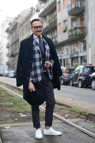 Cómo combinar un abrigo largo negro: Emparejar un abrigo largo negro junto a un pantalón chino en gris oscuro es una opción inigualable para un día en la oficina. Tenis blancos contrastarán muy bien con el resto del conjunto.
