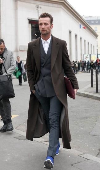 Opta por un abrigo largo marrón oscuro de hombres de Maison Margiela y un pantalón de vestir gris oscuro para un perfil clásico y refinado. ¿Te sientes valiente? Completa tu atuendo con deportivas azules.