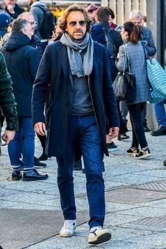 Outfits hombres en invierno 2021: Si buscas un look en tendencia pero clásico, haz de un abrigo largo azul marino y unos vaqueros azul marino tu atuendo. Zapatillas altas de cuero en blanco y azul marino añadirán interés a un estilo clásico. ¡Nos gusta mucho el look! Es una opción excelente para tus jornadas de invierno.