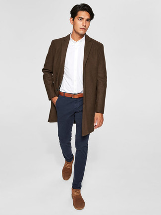 Cómo combinar: abrigo largo en marrón oscuro, camisa de vestir blanca, pantalón chino negro, botas safari de ante marrónes