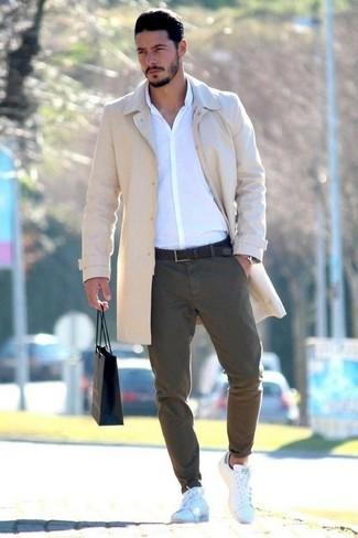Cómo combinar: abrigo largo en beige, camisa de vestir blanca, pantalón chino verde oliva, tenis de cuero blancos