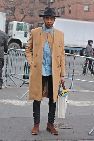 Cómo combinar: abrigo largo marrón claro, camisa vaquera celeste, vaqueros negros, botines chelsea de ante marrónes