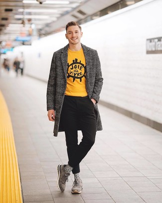 Cómo combinar: abrigo largo de pata de gallo gris, camiseta con cuello circular estampada amarilla, pantalón chino negro, deportivas de ante grises