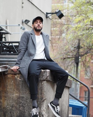 Cómo combinar: abrigo largo gris, camiseta con cuello circular blanca, pantalón de chándal negro, tenis de lona en negro y blanco