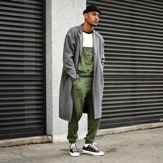 Cómo combinar: abrigo largo gris, camiseta con cuello circular blanca, peto verde oliva, tenis de lona en negro y blanco