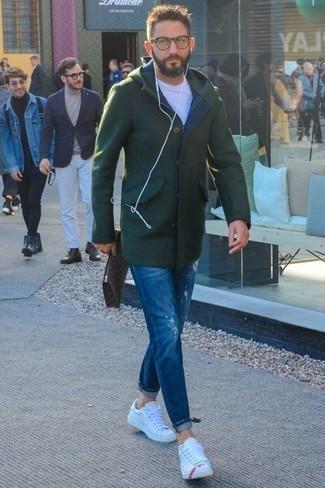 Outfits hombres en clima fresco estilo casuale: Elige un abrigo largo verde oscuro y unos vaqueros desgastados azules para un look diario sin parecer demasiado arreglada. Tenis de cuero blancos son una opción inigualable para complementar tu atuendo.