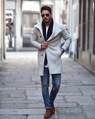 Cómo combinar: abrigo largo gris, camiseta de manga larga blanca, vaqueros pitillo desgastados azules, botines chelsea de ante marrónes