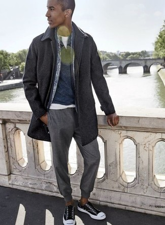 Cómo combinar un abrigo largo en gris oscuro: Considera emparejar un abrigo largo en gris oscuro junto a un pantalón chino gris para las 8 horas. Si no quieres vestir totalmente formal, opta por un par de tenis de lona en negro y blanco.