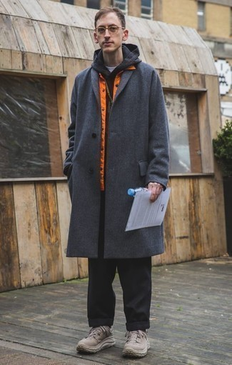 Cómo combinar un abrigo largo en gris oscuro: Algo tan simple como emparejar un abrigo largo en gris oscuro con un pantalón chino negro puede distinguirte de la multitud. Haz este look más informal con deportivas marrón claro.