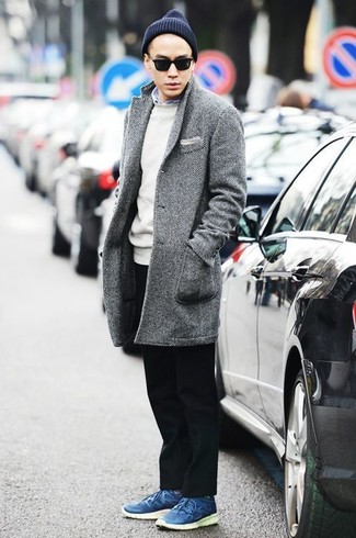 Outfits hombres: Haz de un abrigo largo de espiguilla gris y un pantalón chino negro tu atuendo para lograr un estilo informal elegante. ¿Quieres elegir un zapato informal? Usa un par de tenis de cuero azules para el día.