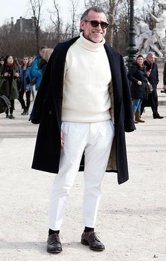 Cómo combinar: abrigo largo negro, jersey de cuello alto blanco, pantalón chino blanco, zapatos derby de cuero en marrón oscuro