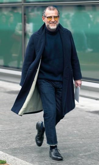Cómo combinar: abrigo largo negro, jersey de cuello alto de punto negro, vaqueros azul marino, zapatos derby de cuero negros