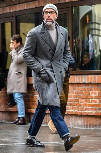 Cómo combinar: abrigo largo gris, jersey de cuello alto gris, vaqueros azules, zapatos con doble hebilla de cuero negros