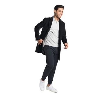 Cómo combinar: abrigo largo negro, camisa polo gris, pantalón de chándal negro, tenis de cuero blancos