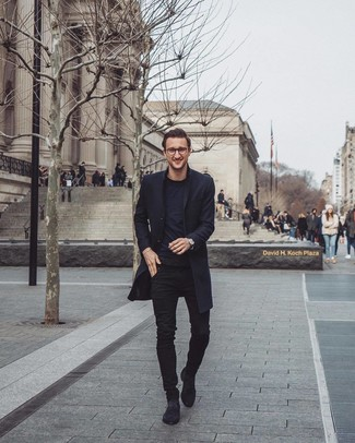 Cómo combinar: abrigo largo negro, camiseta con cuello circular negra, vaqueros pitillo negros, botines chelsea de ante negros