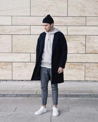 Cómo combinar un abrigo largo negro: Utiliza un abrigo largo negro y un pantalón chino de lana gris para las 8 horas. Si no quieres vestir totalmente formal, completa tu atuendo con tenis de cuero blancos.