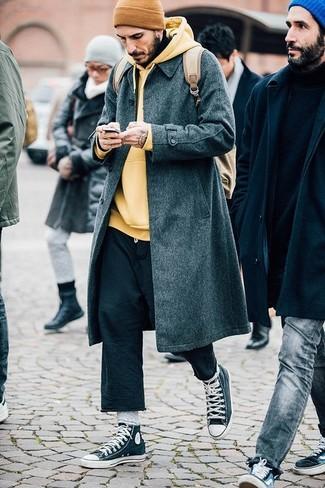 Cómo combinar: abrigo largo en gris oscuro, sudadera con capucha amarilla, pantalón chino negro, zapatillas altas en gris oscuro