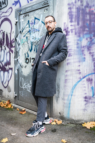 Cómo combinar: abrigo largo gris, sudadera con capucha estampada negra, pantalón de vestir de lana gris, deportivas negras