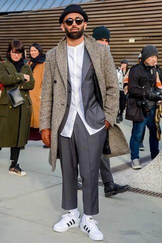 Cómo combinar unos tenis de cuero en blanco y negro: Empareja un abrigo largo de espiguilla marrón con un traje de rayas verticales gris para una apariencia clásica y elegante. Mezcle diferentes estilos con tenis de cuero en blanco y negro.