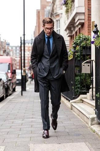 Cómo combinar: abrigo largo en gris oscuro, traje de lana en gris oscuro, camisa de vestir de cambray azul, zapatos con doble hebilla de cuero en marrón oscuro