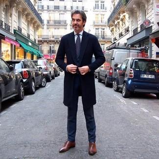 Cómo combinar: abrigo largo negro, traje negro, camisa de vestir blanca, zapatos oxford de cuero marrónes